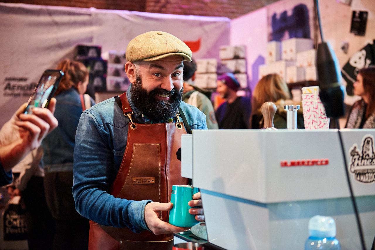 Barista steaming milk on La Marzocco coffee machine