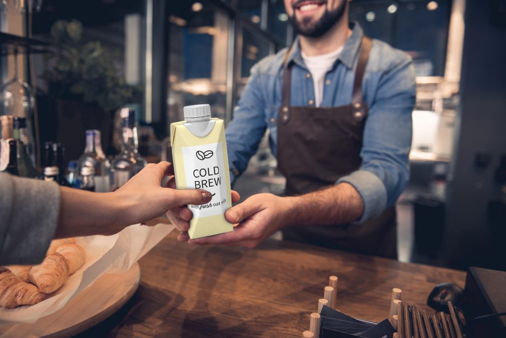 A barista hands a carton of cold brew coffee to a customer