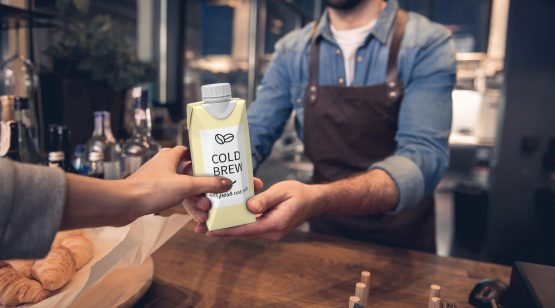 A barista hands a customer a carton of cold-brew coffee