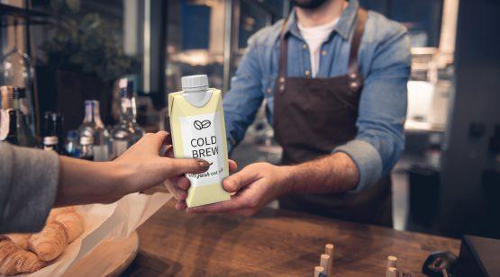 A barista hands a customer a carton of cold-brew coffee