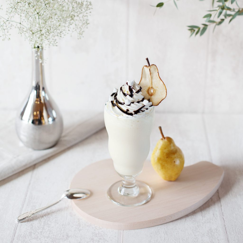 A striking shot of a tempting white smoothie decorated with an ornate pear