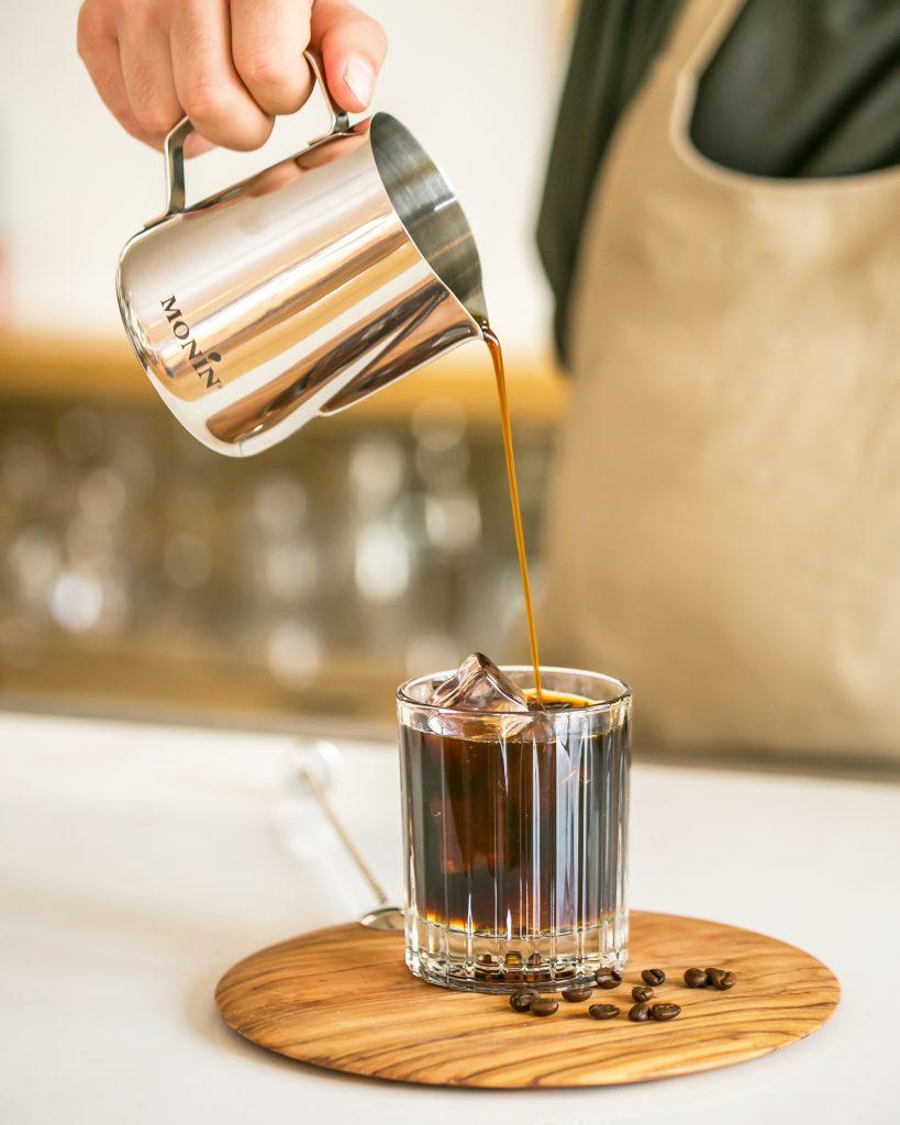 A barista serves a MONIN cold brew cocktail