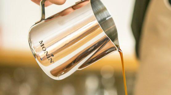 A barista pouring cold-brew coffee