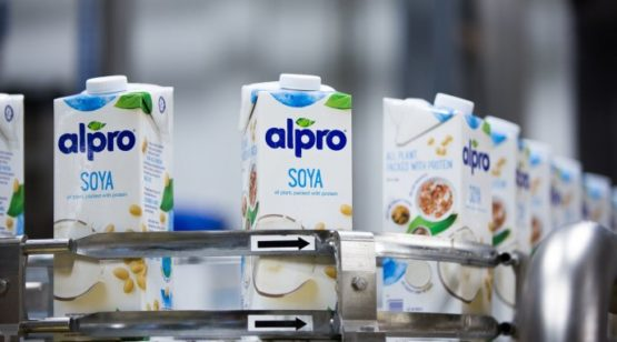 Cartons of Alpro Soya beverage on conveyer belt in processing facility.